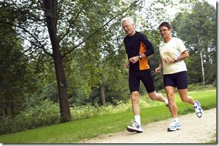 Senior Couple Running In The Woods