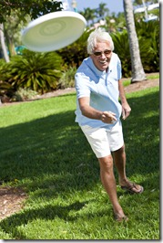 Happy Senior Man Throwing Frisbee Outside in Sunshine